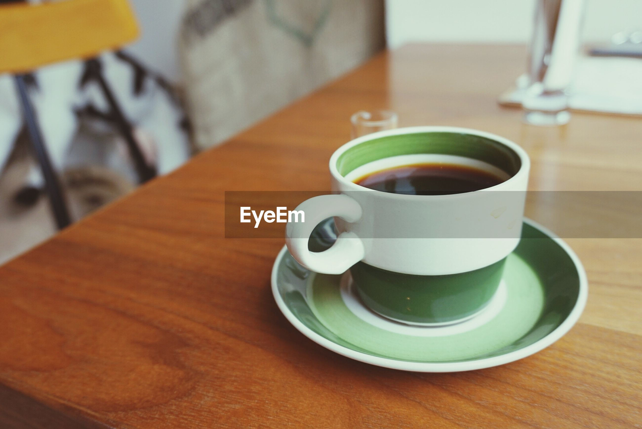 drink, coffee cup, refreshment, table, food and drink, saucer, indoors, coffee - drink, freshness, coffee, cup, still life, wood - material, close-up, beverage, tea cup, frothy drink, spoon, high angle view, tea