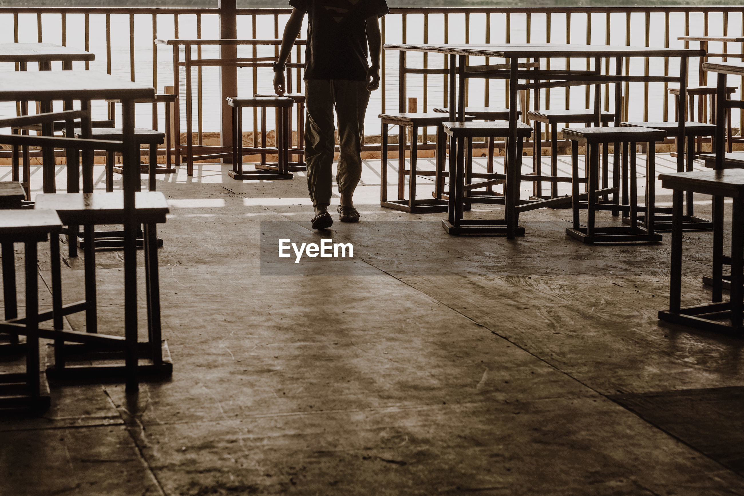LOW SECTION OF MAN STANDING ON TABLE IN EMPTY ROOM