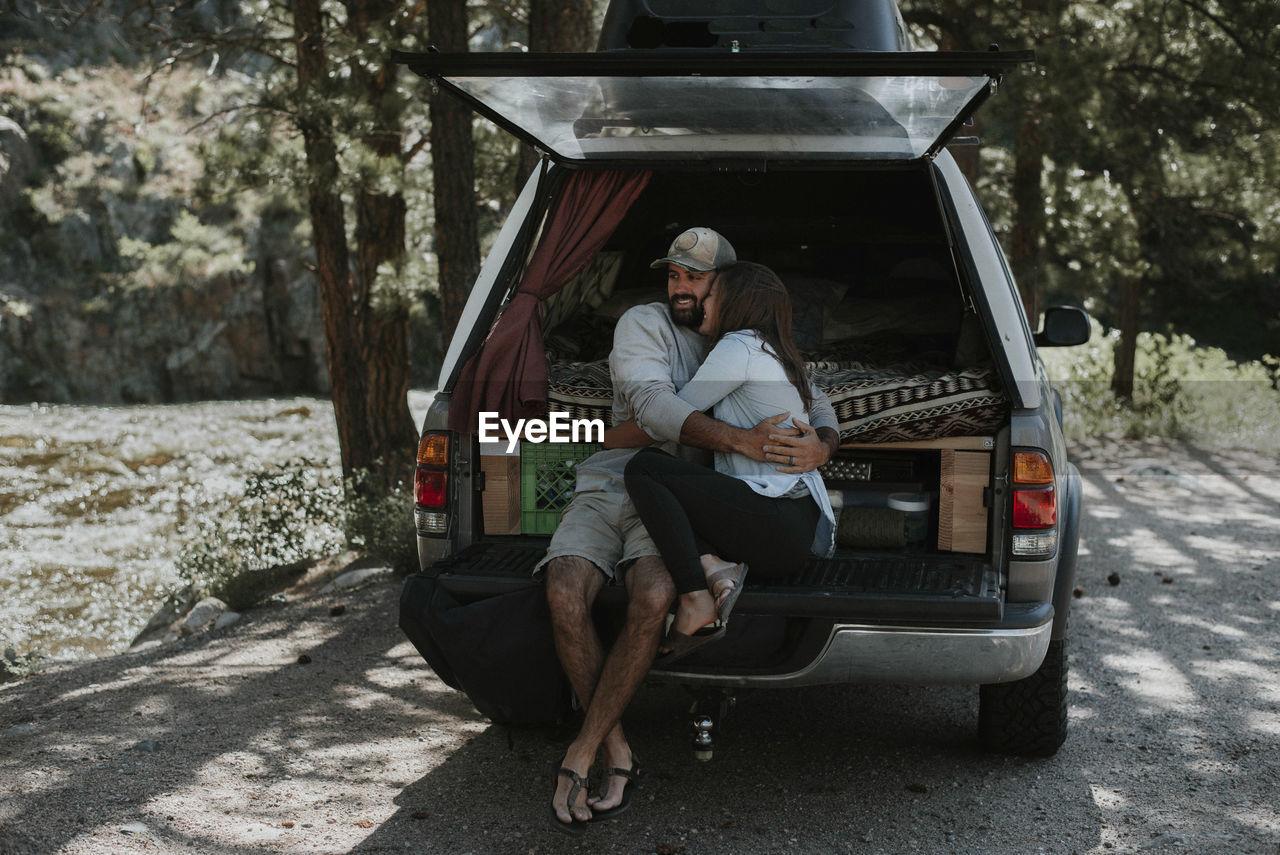 FULL LENGTH OF MAN SITTING ON CAR AT PARK