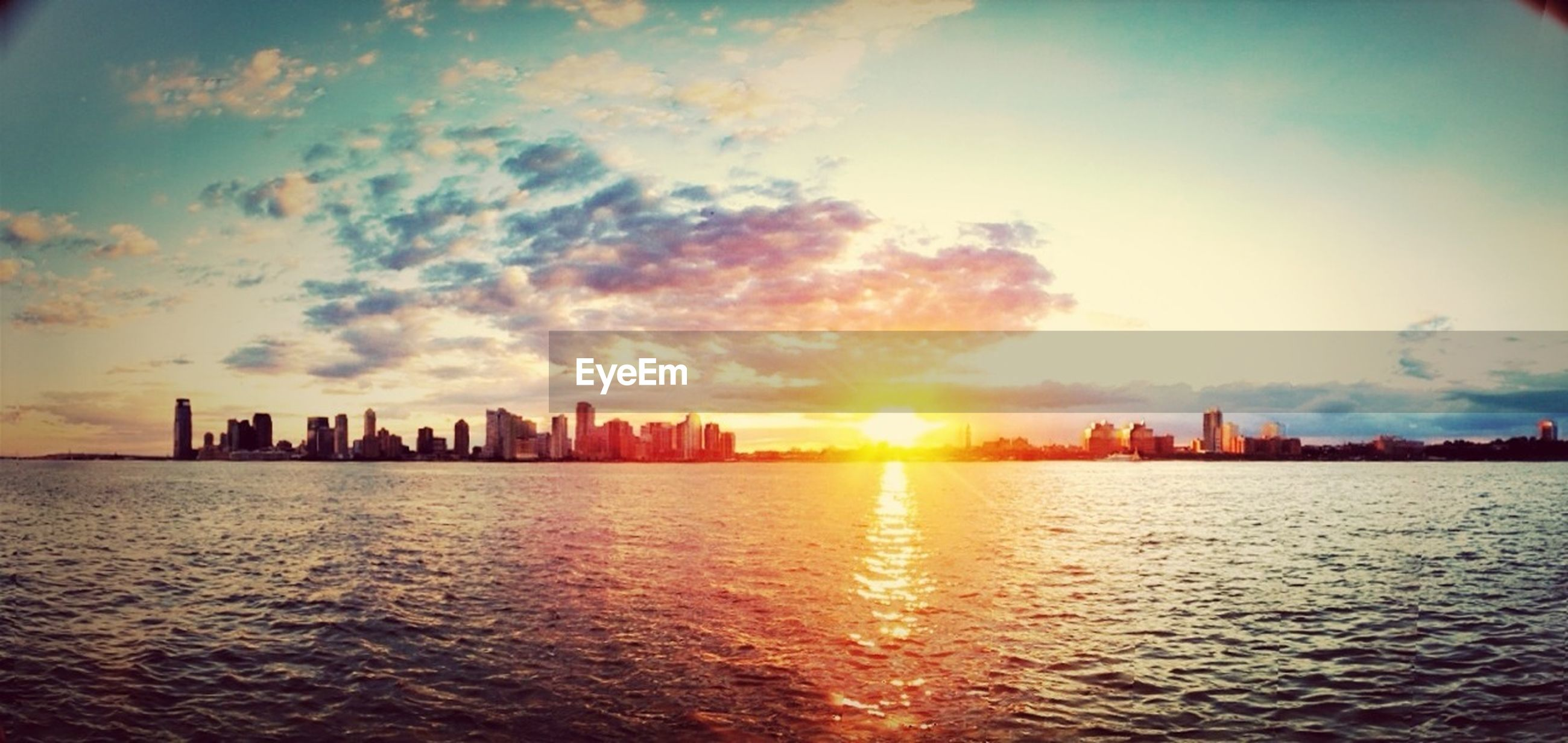 building exterior, sunset, waterfront, architecture, water, built structure, sky, city, sun, silhouette, urban skyline, cityscape, cloud - sky, sea, skyscraper, sunlight, rippled, scenics, reflection, cloud