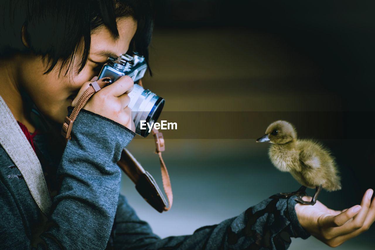 Close-Up Of Girl Photographing Bird