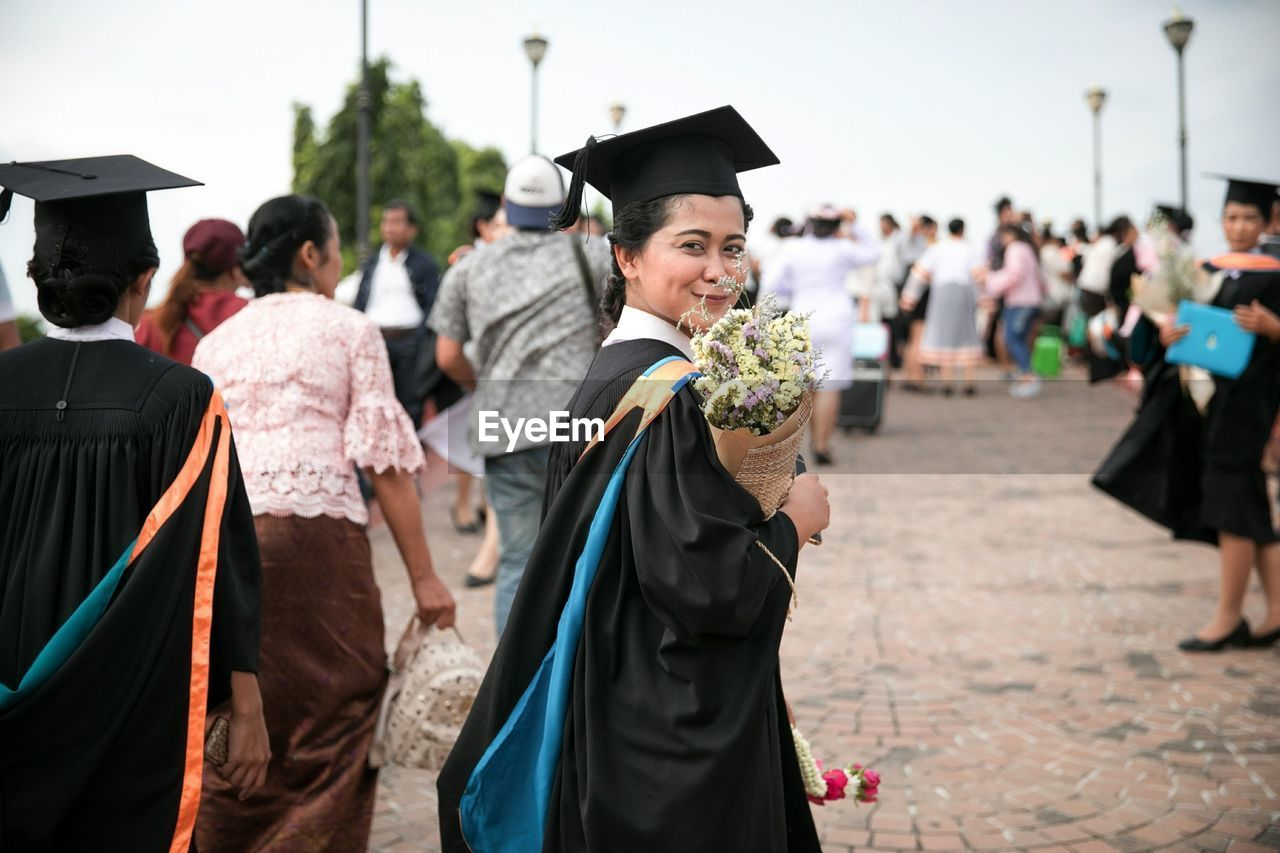 Smiling Woman In Graduation Gown Walking With Crowd On Street