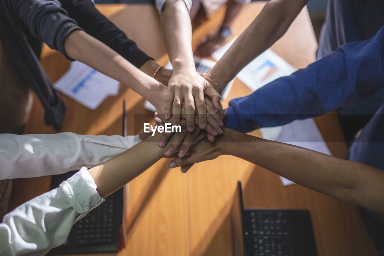 High angle view of business colleagues stacking hands in office