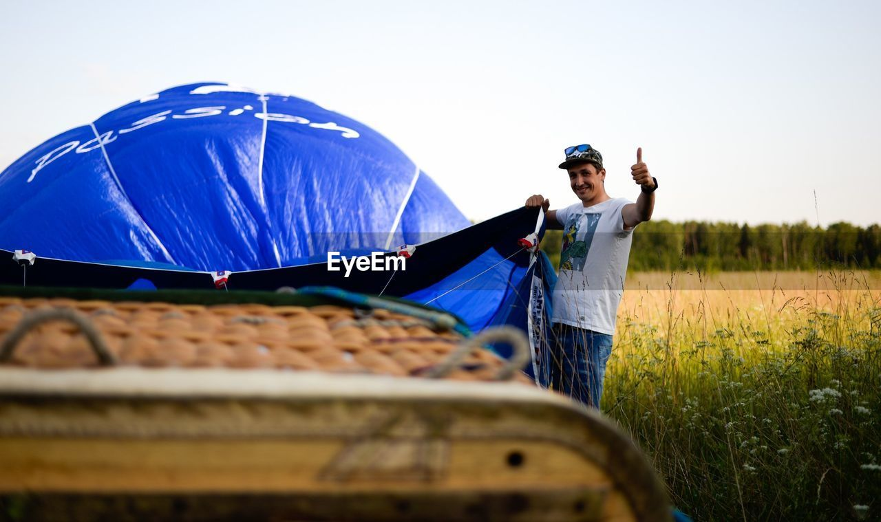 Portrait of man showing thumbs up while putting up tent on field