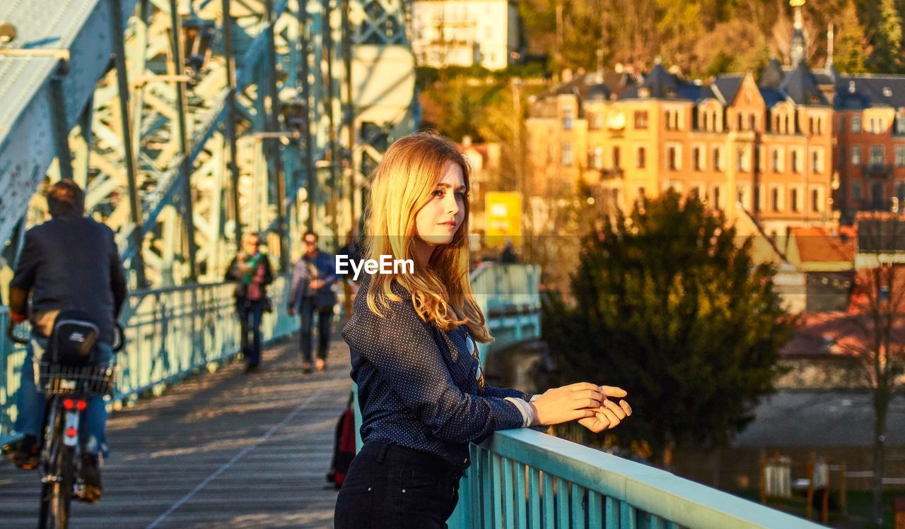 Woman looking away while standing by railing in city