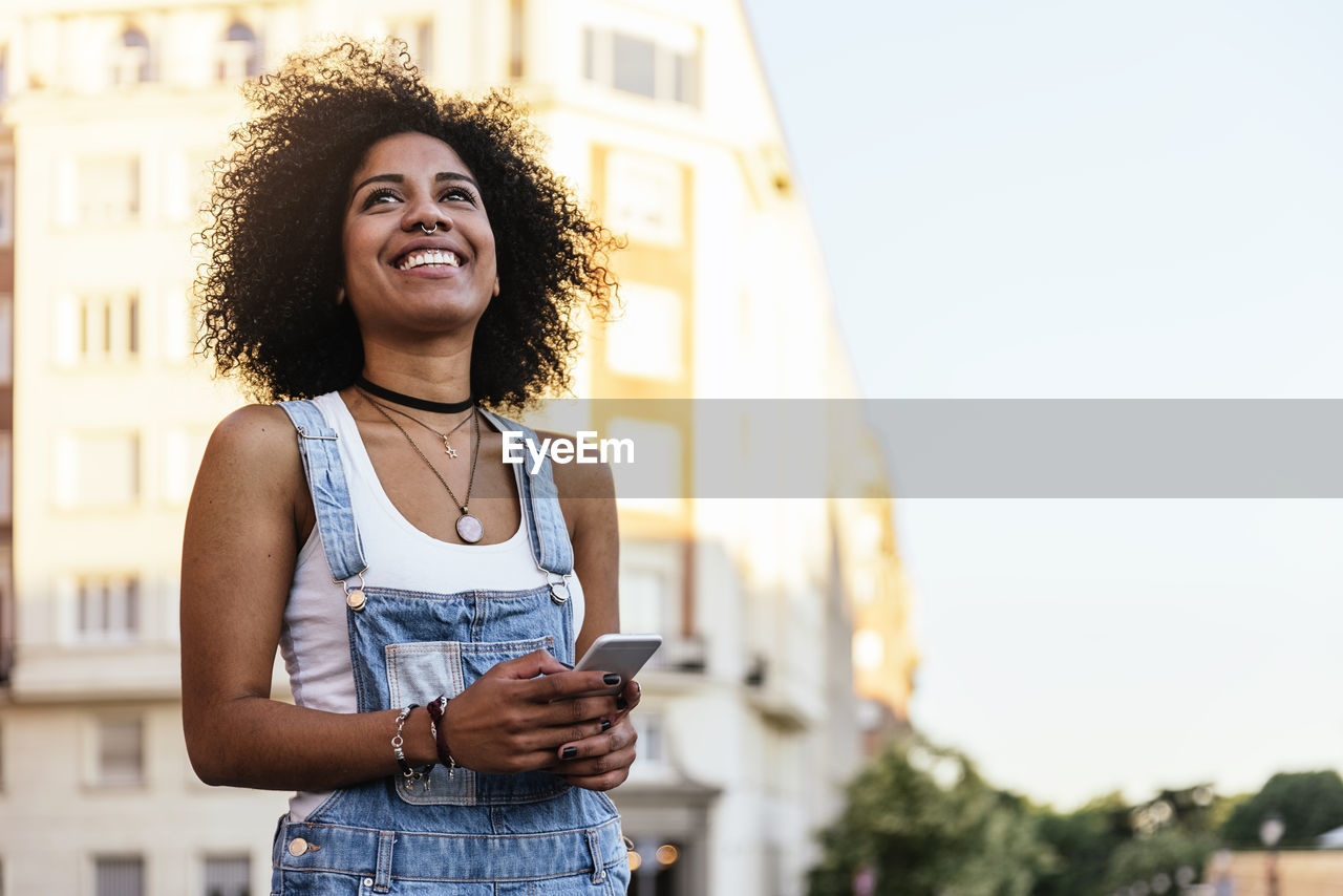 Smiling Woman With Phone Standing Against Building