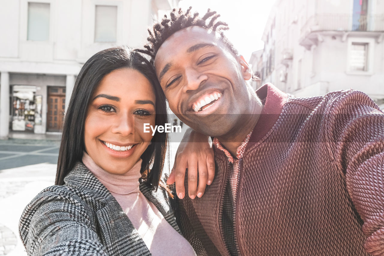 smiling, happiness, portrait, two people, emotion, young adult, looking at camera, togetherness, real people, young men, architecture, young women, bonding, toothy smile, teeth, leisure activity, headshot, casual clothing, lifestyles, adult, positive emotion, couple - relationship, arm around, outdoors, warm clothing, scarf