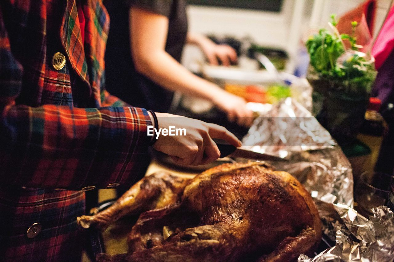 Midsection of person holding kitchen knife on thanksgiving turkey at home