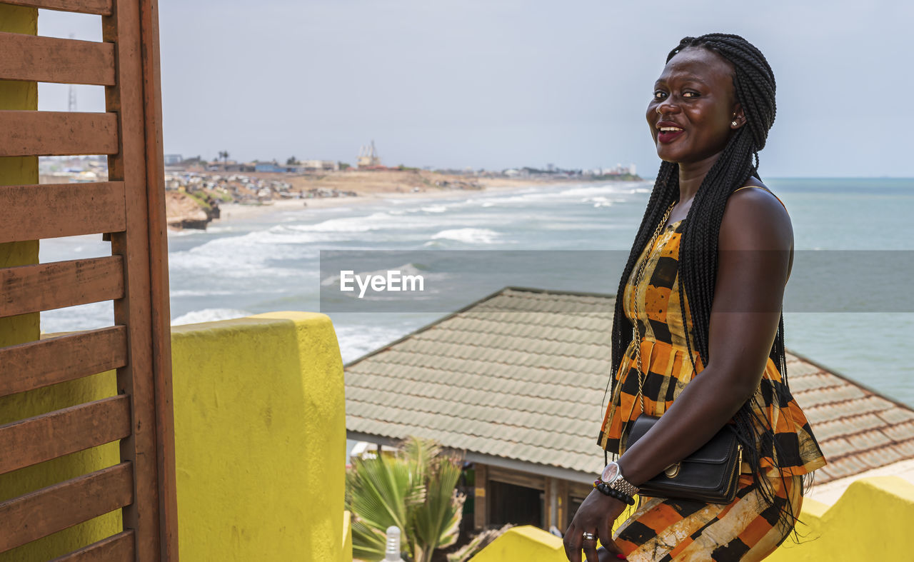 Africa woman from ghana is happy at an entrance to a seafront restaurant in accra ghana west africa.