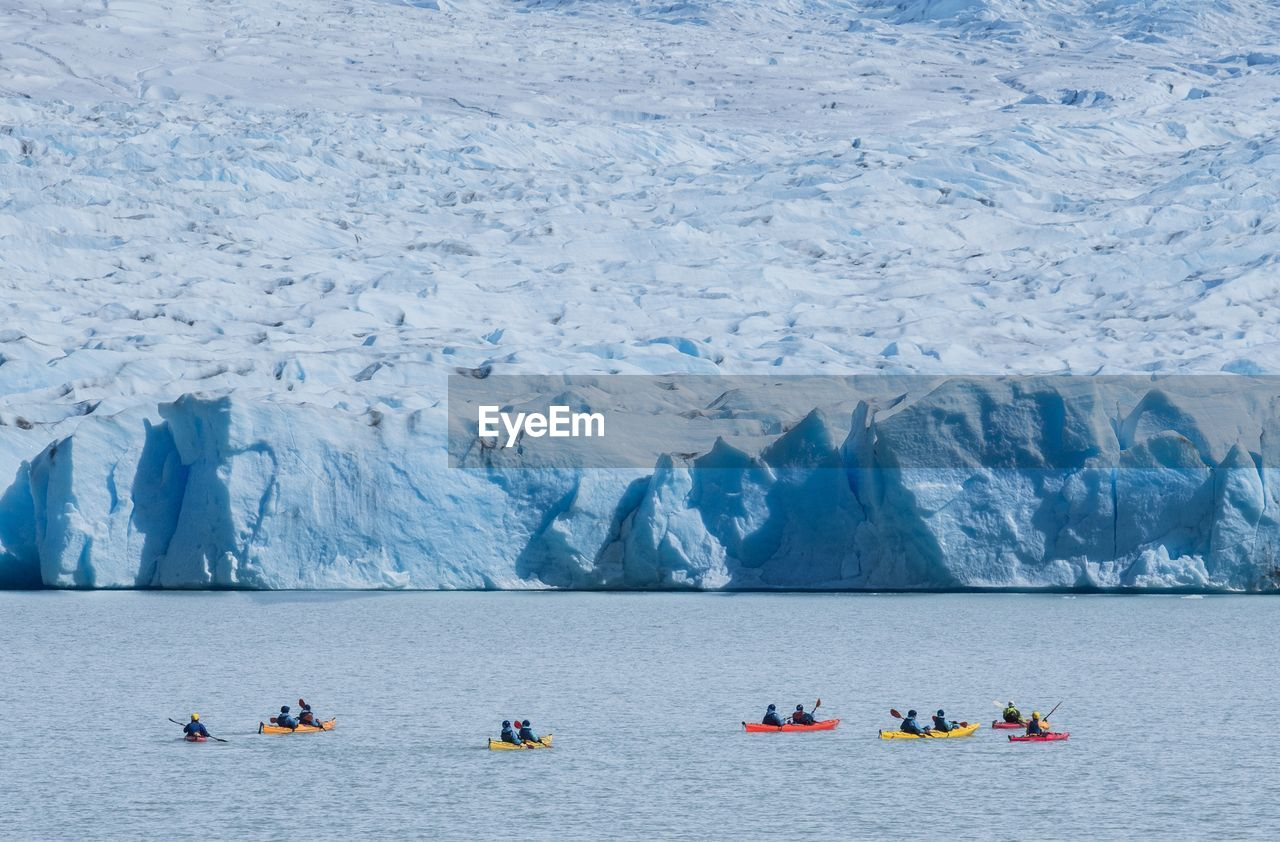 High angle view of people on boats sailing in glacier lake