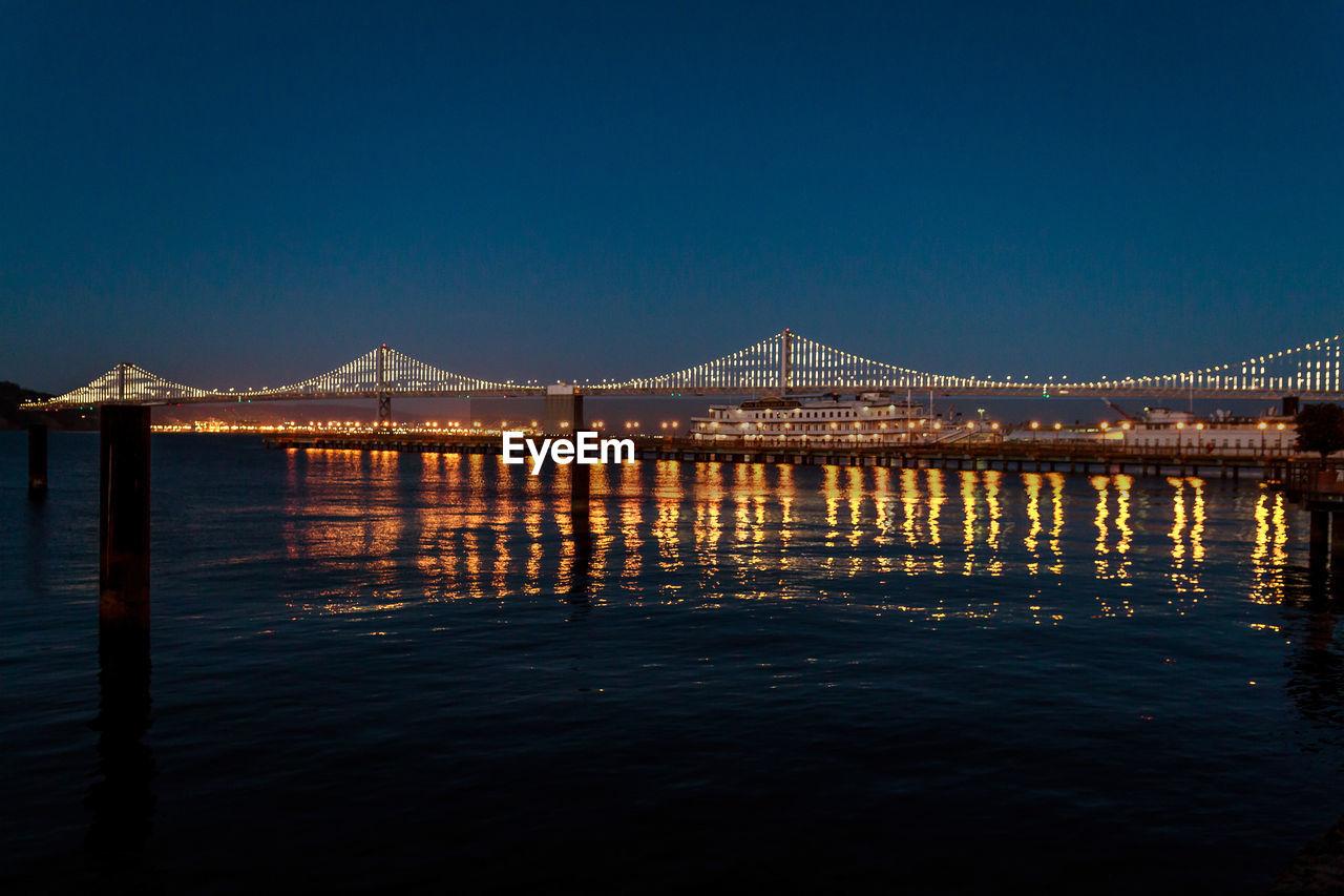 Illuminated golden gate bridge over sea against sky at night