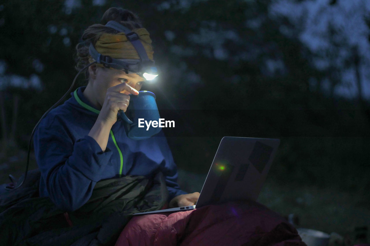 Woman Using Laptop While Camping On Field At Dusk