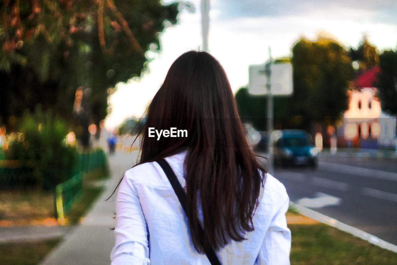 Rear view of woman with long hair walking on sidewalk