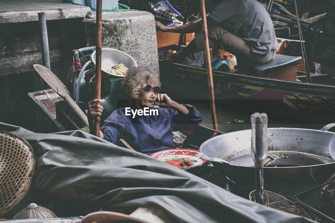 Senior woman sitting on floating market at river