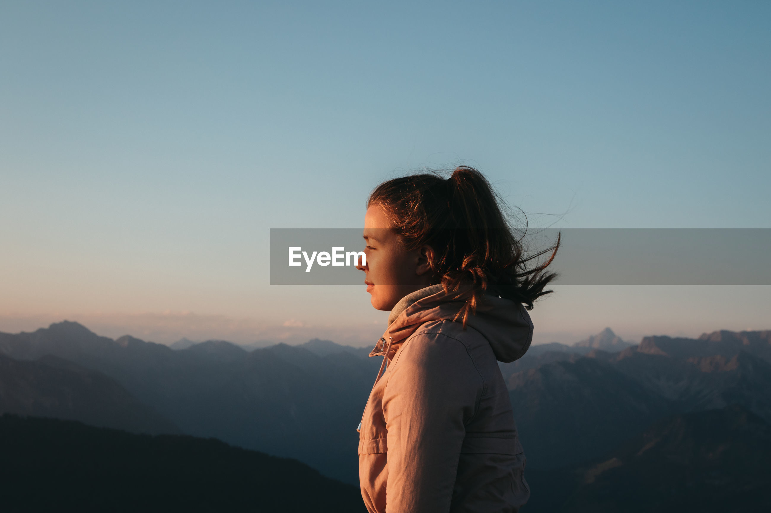 Woman standing on mountain against clear sky during sunrise