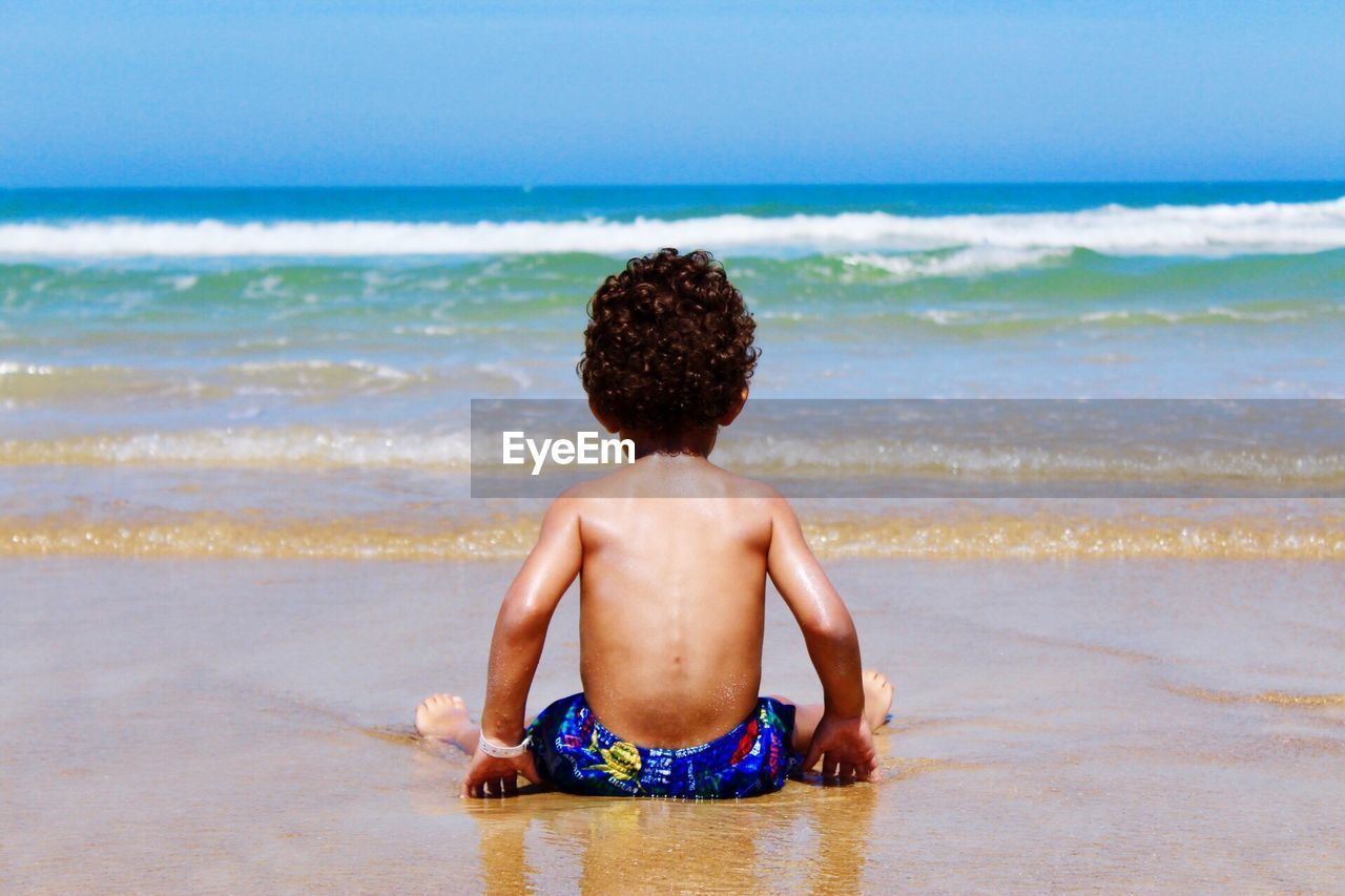 Rear View Of Shirtless Boy On Beach