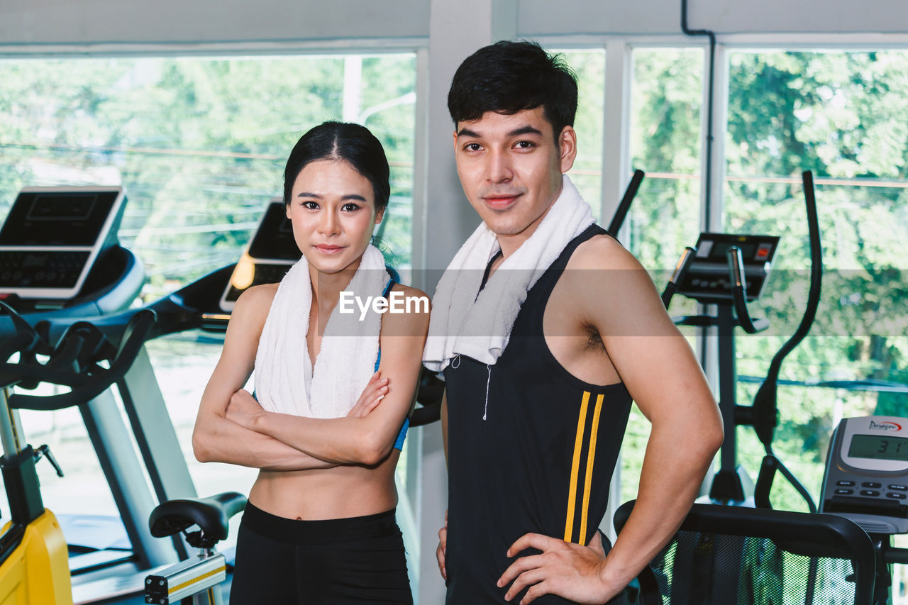 Portrait Of Young Man And Woman Standing At Gym