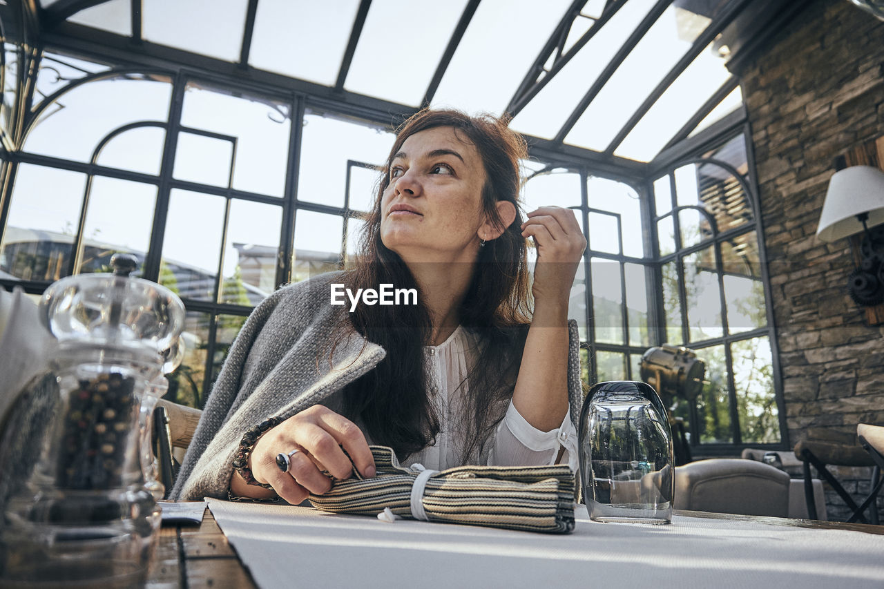 Thoughtful Woman Sitting At Table In Restaurant