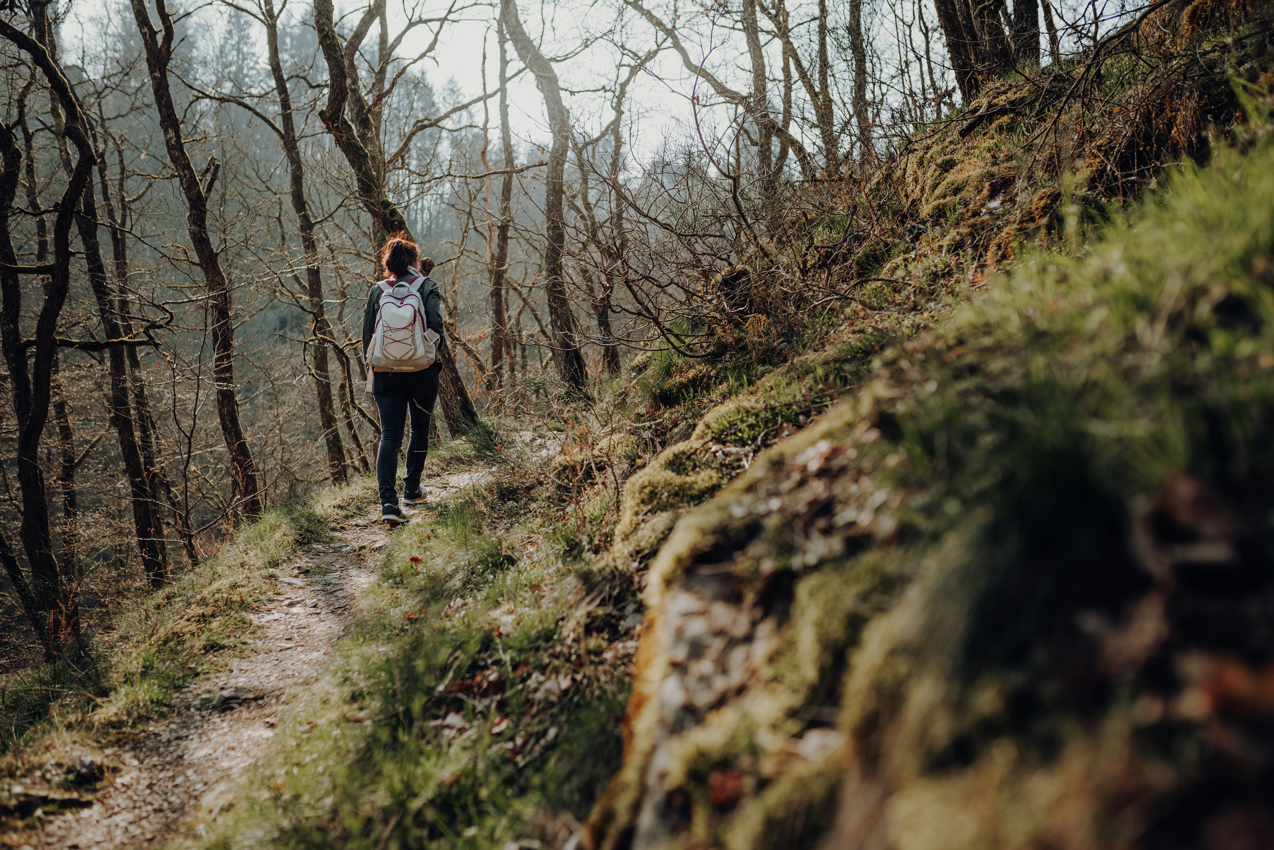 WOMAN WALKING ON FOOTPATH IN FOREST