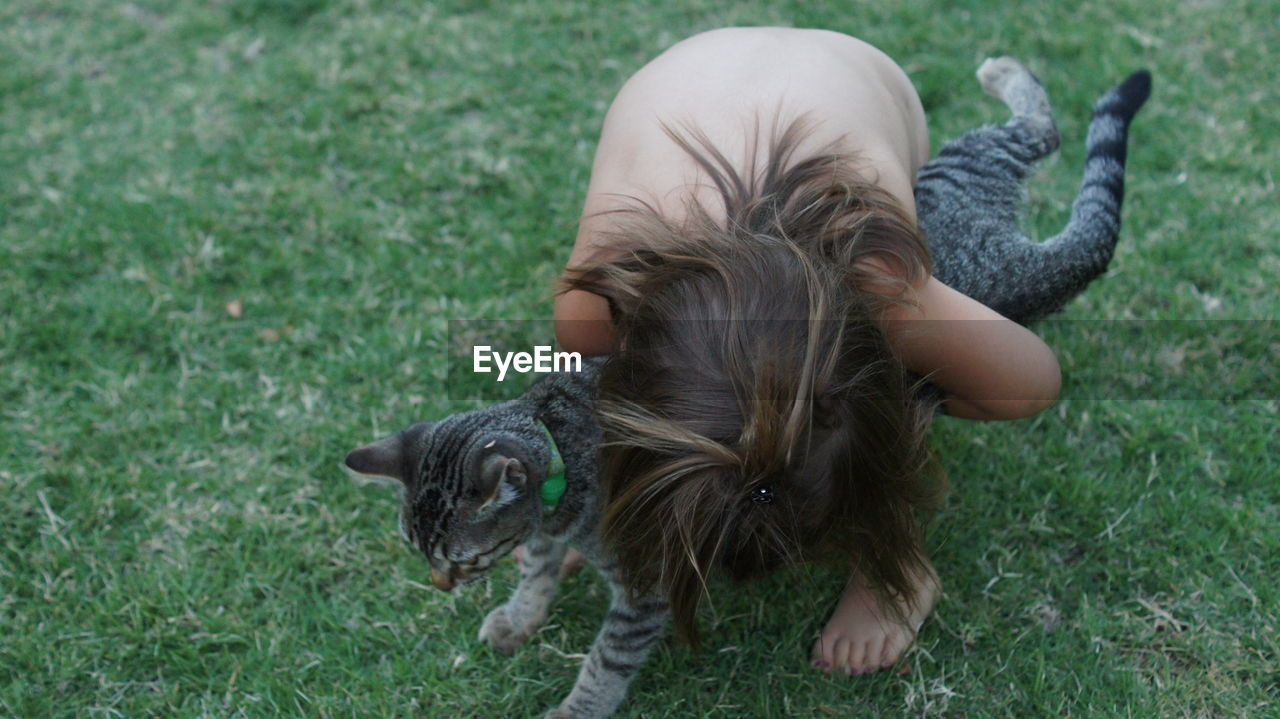 High Angle View Of Shirtless Girl Hugging Her Pet Cat On Field