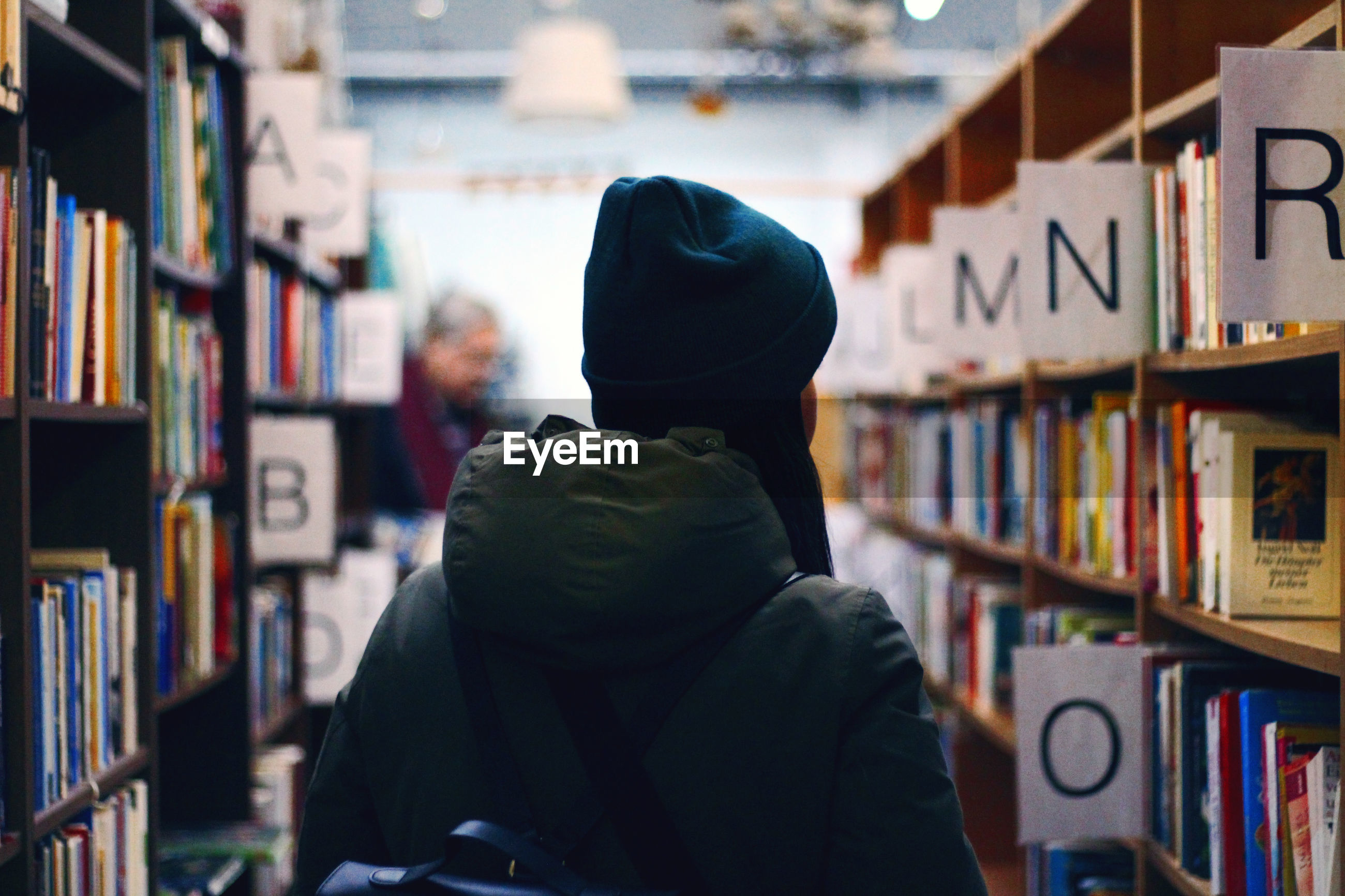 REAR VIEW OF PEOPLE READING BOOK IN SHELF