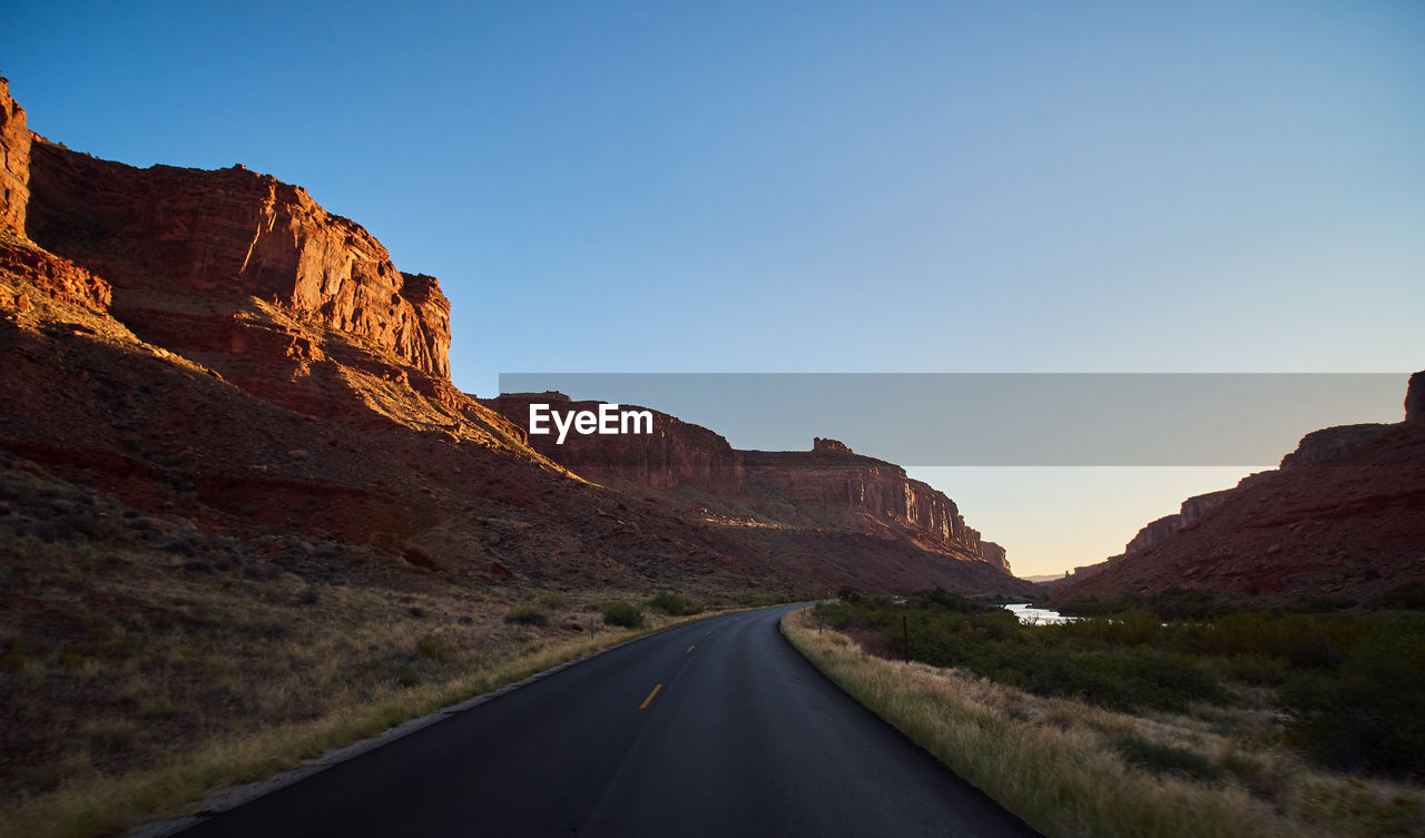 road, mountain, direction, the way forward, transportation, nature, rock, tranquil scene, beauty in nature, sky, non-urban scene, scenics - nature, rock - object, tranquility, no people, rock formation, clear sky, environment, landscape, solid, mountain range, diminishing perspective, formation, outdoors