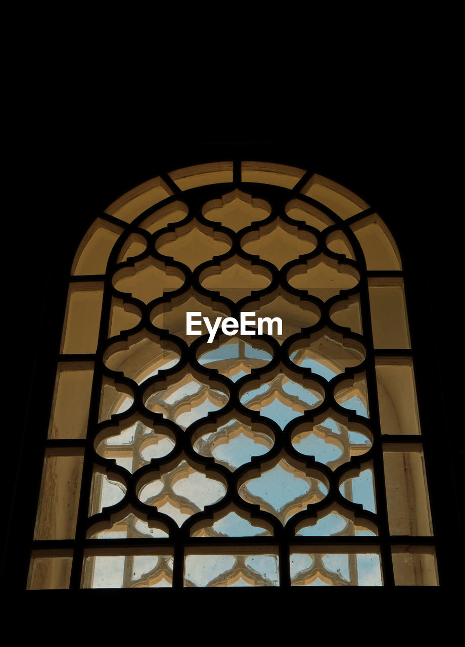 window, pattern, indoors, glass - material, no people, design, architecture, stained glass, low angle view, built structure, dark, shape, silhouette, geometric shape, copy space, glass, transparent, close-up, illuminated, ornate, floral pattern, ceiling, window frame