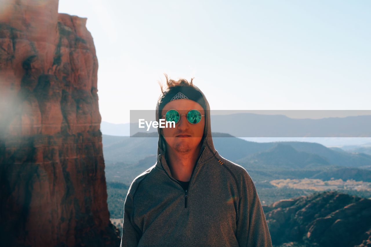 Portrait Of Young Man Wearing Sunglasses While Standing On Mountain Against Sky