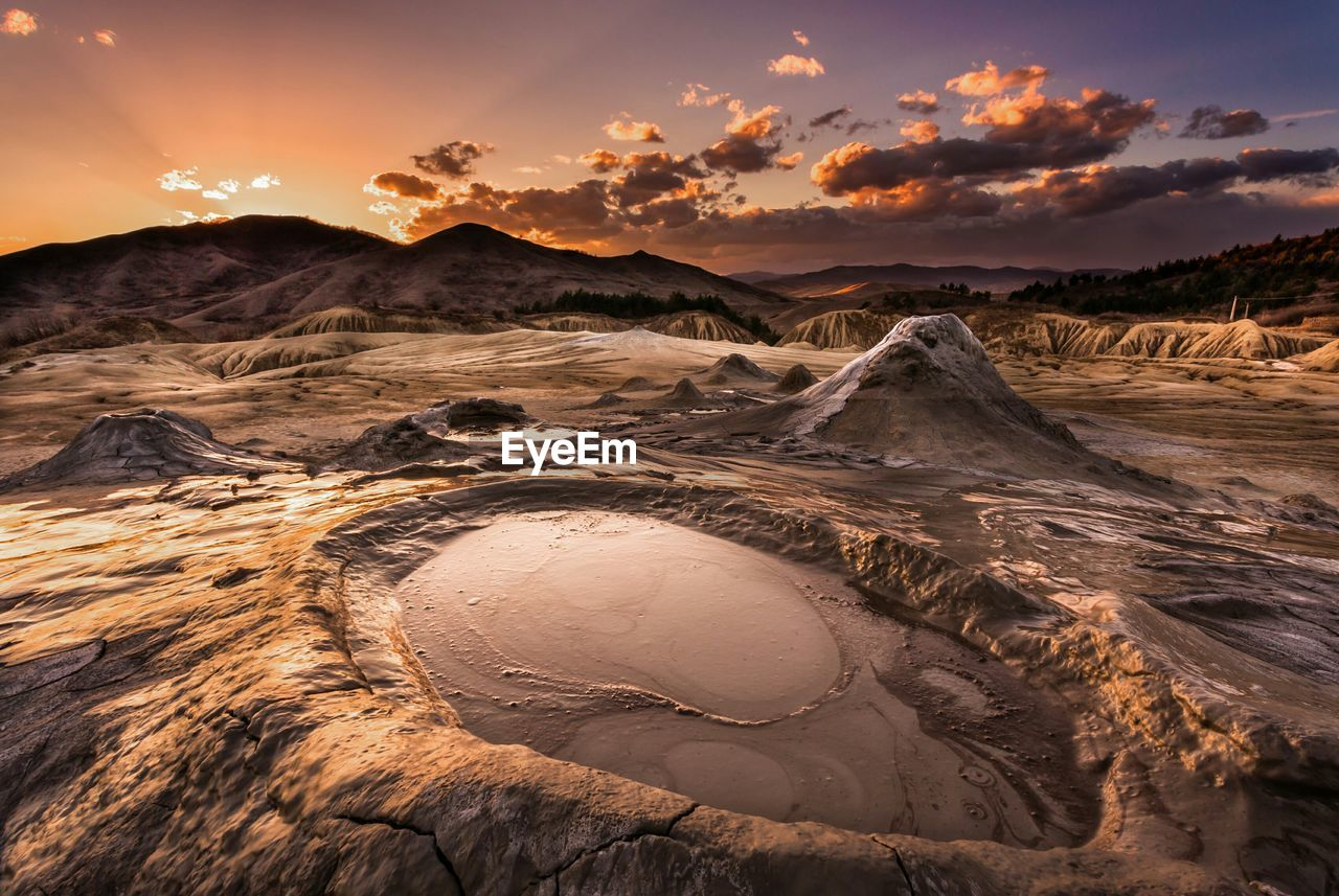 Scenic view of berca mud volcanoes against sky during sunset