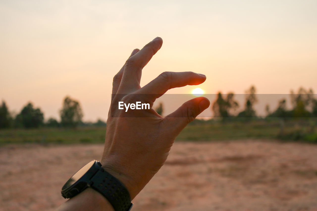 Optical illusion of hand holding sun during sunset