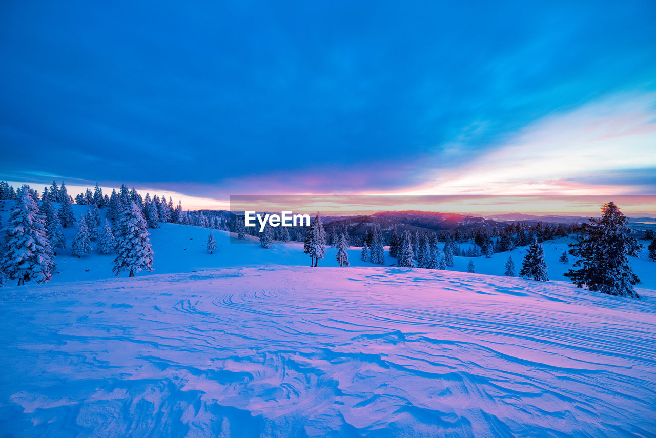 Snow Covered Landscape Against Cloudy Sky During Sunset