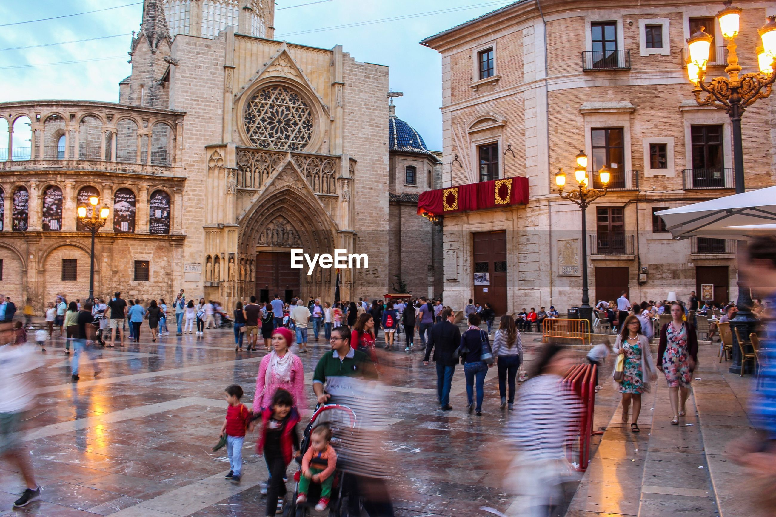 building exterior, large group of people, architecture, built structure, person, city, lifestyles, men, city life, leisure activity, wet, crowd, illuminated, travel destinations, tourist, culture, tourism, in front of, famous place, outdoors, place of worship