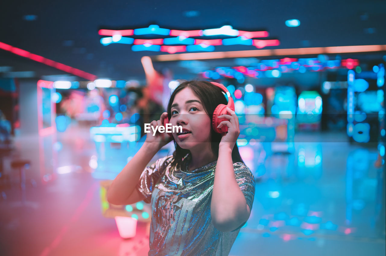 Young woman listening music while standing in illuminated room