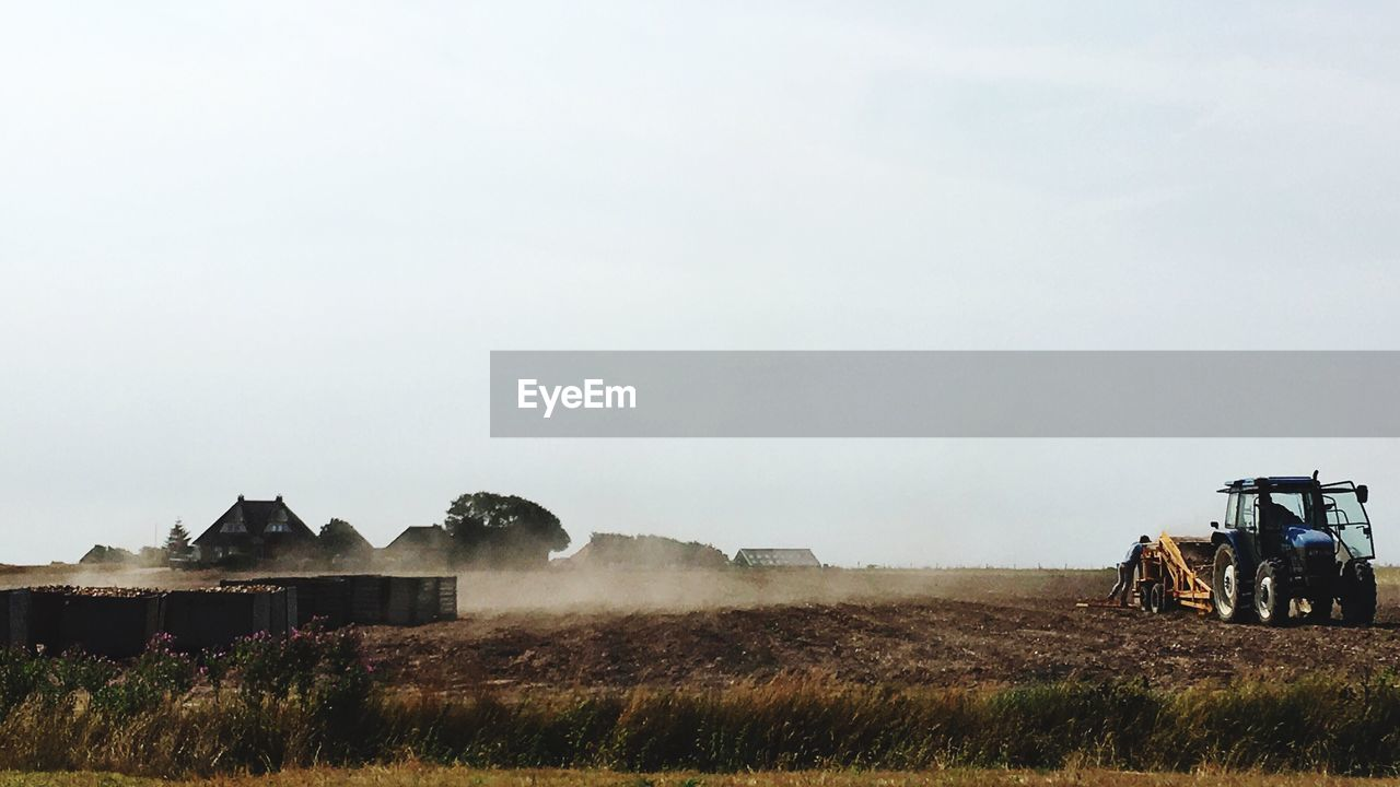 sky, field, building exterior, environment, land, nature, plant, landscape, day, built structure, architecture, farm, no people, rural scene, agriculture, grass, machinery, copy space, fog, building, outdoors