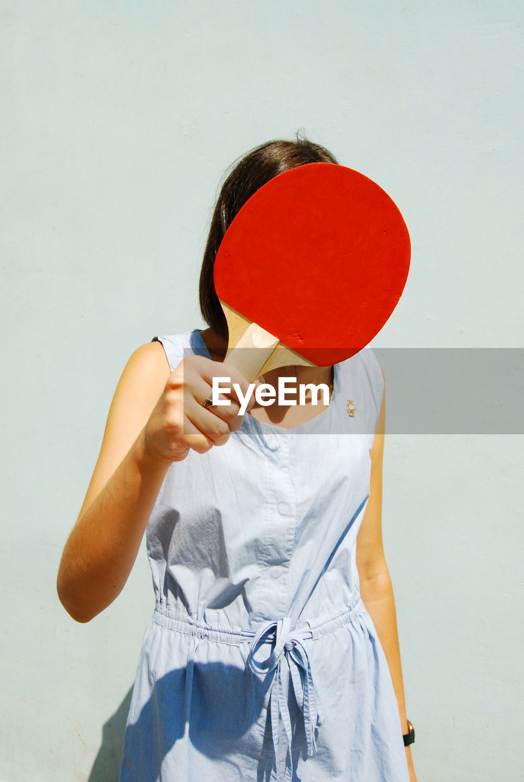one person, holding, front view, red, leisure activity, obscured face, standing, wall - building feature, casual clothing, lifestyles, real people, indoors, three quarter length, women, studio shot, hiding, balloon, unrecognizable person, covering, human face, hairstyle