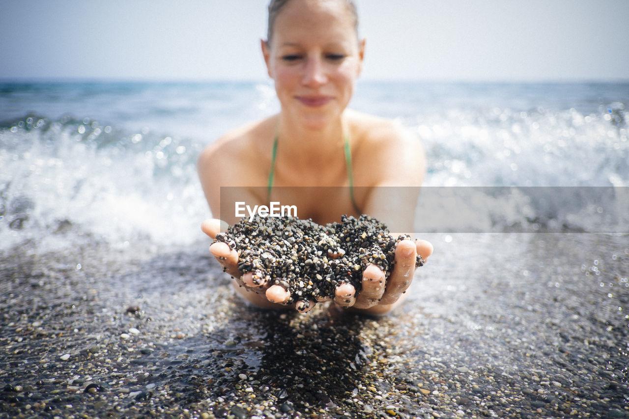 Woman holding wet black sand on seashore