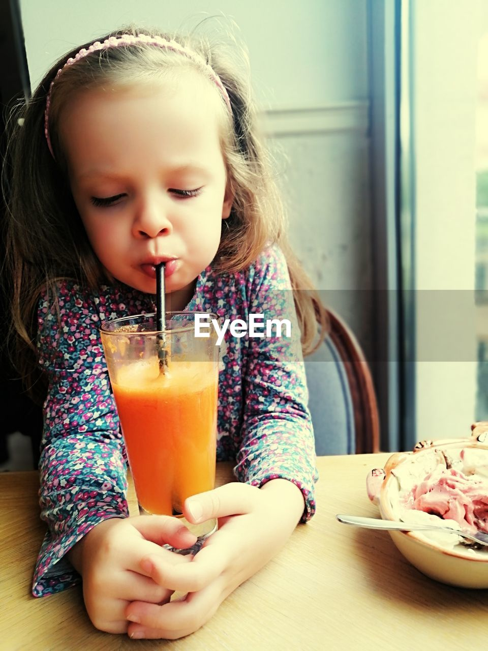 MID SECTION OF A GIRL DRINKING GLASS WITH DRINK