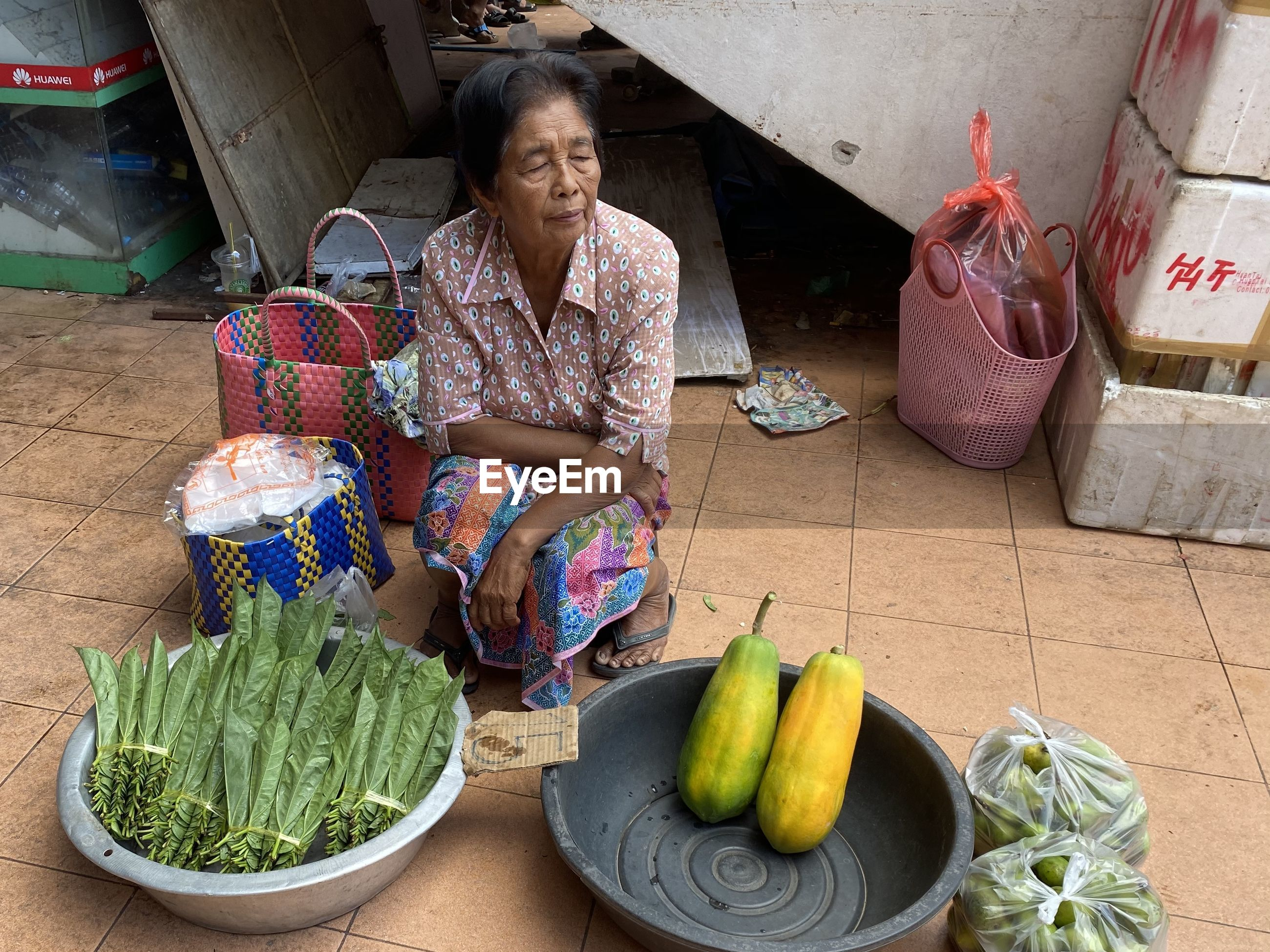 WOMAN SITTING WITH VEGETABLES FOR SALE AT MARKET STALL
