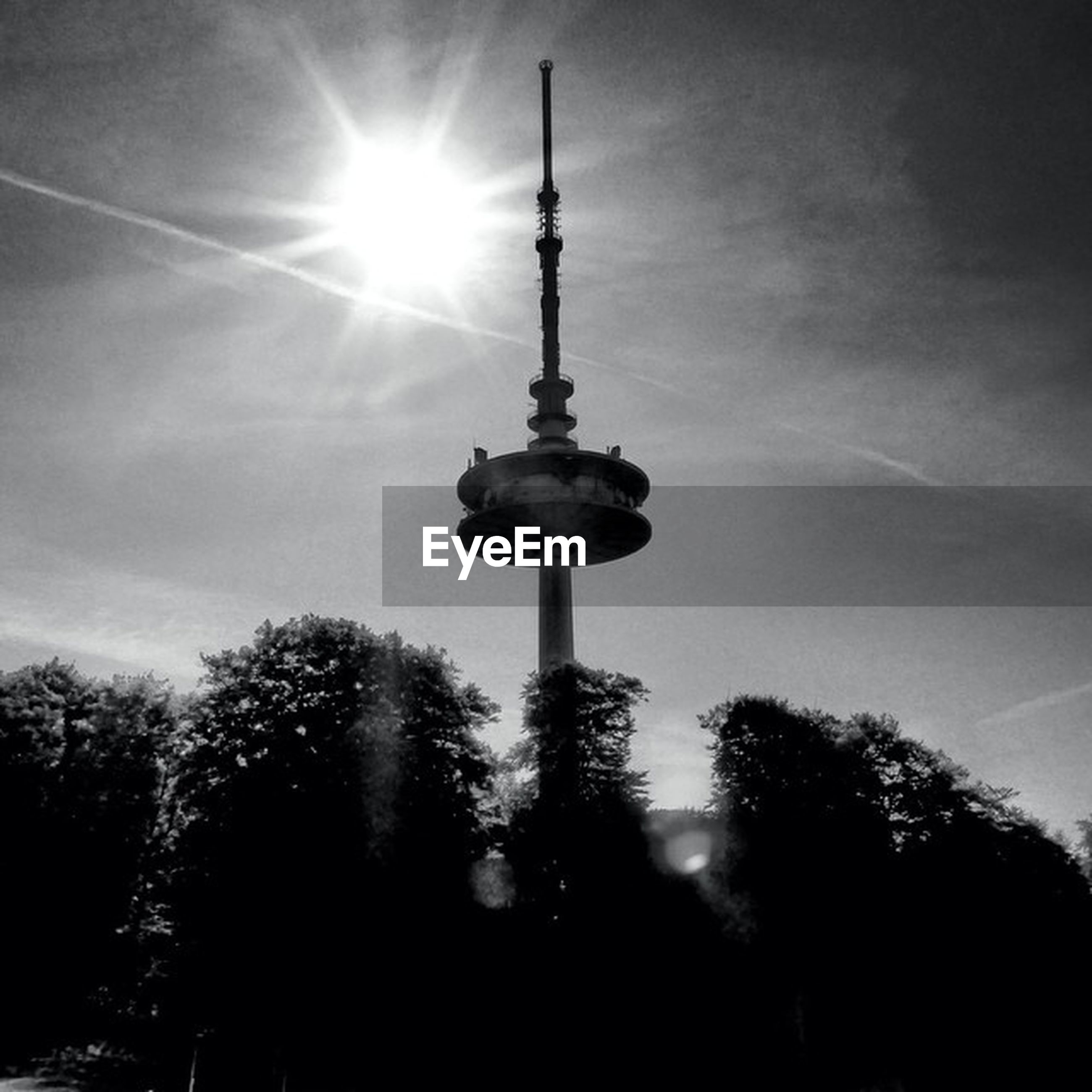 communications tower, low angle view, sky, tall - high, tree, tower, cloud - sky, television tower, silhouette, fernsehturm, communication, sphere, spire, sun, travel destinations, culture, street light, international landmark, tourism, sunlight