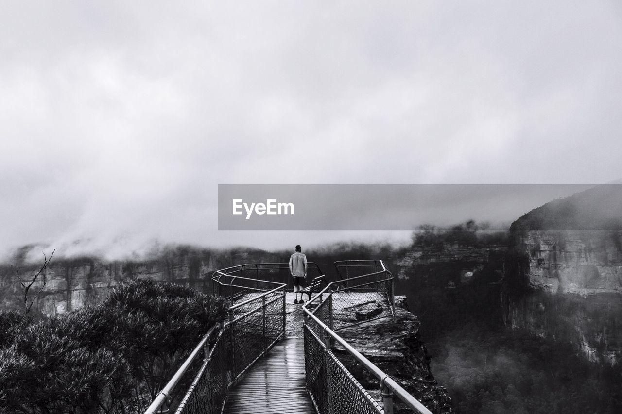 Rear View Of Man Standing At Observation Point In Blue Mountains National Park During Foggy Weather