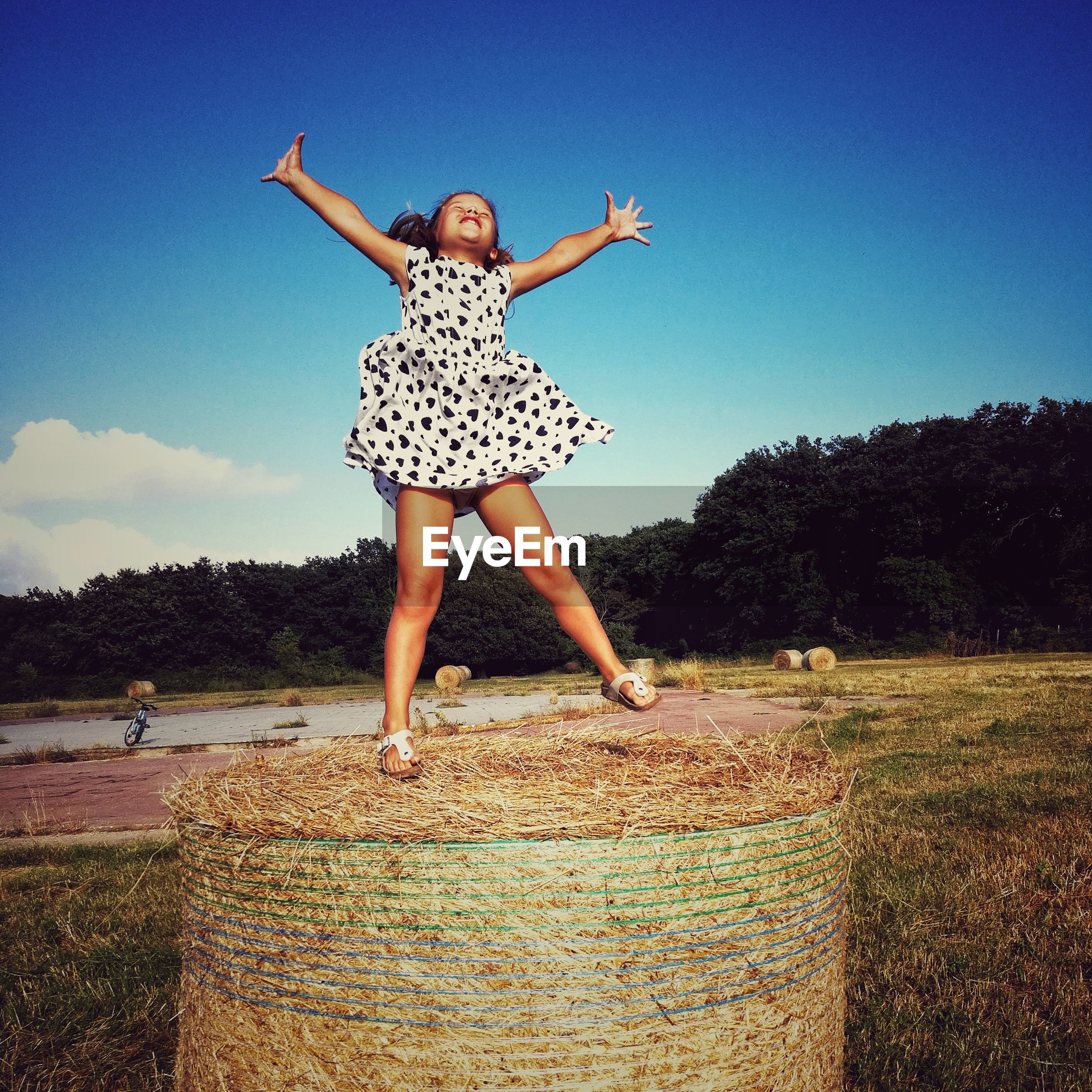 Full length of carefree girl with arms outstretched standing on hay bale