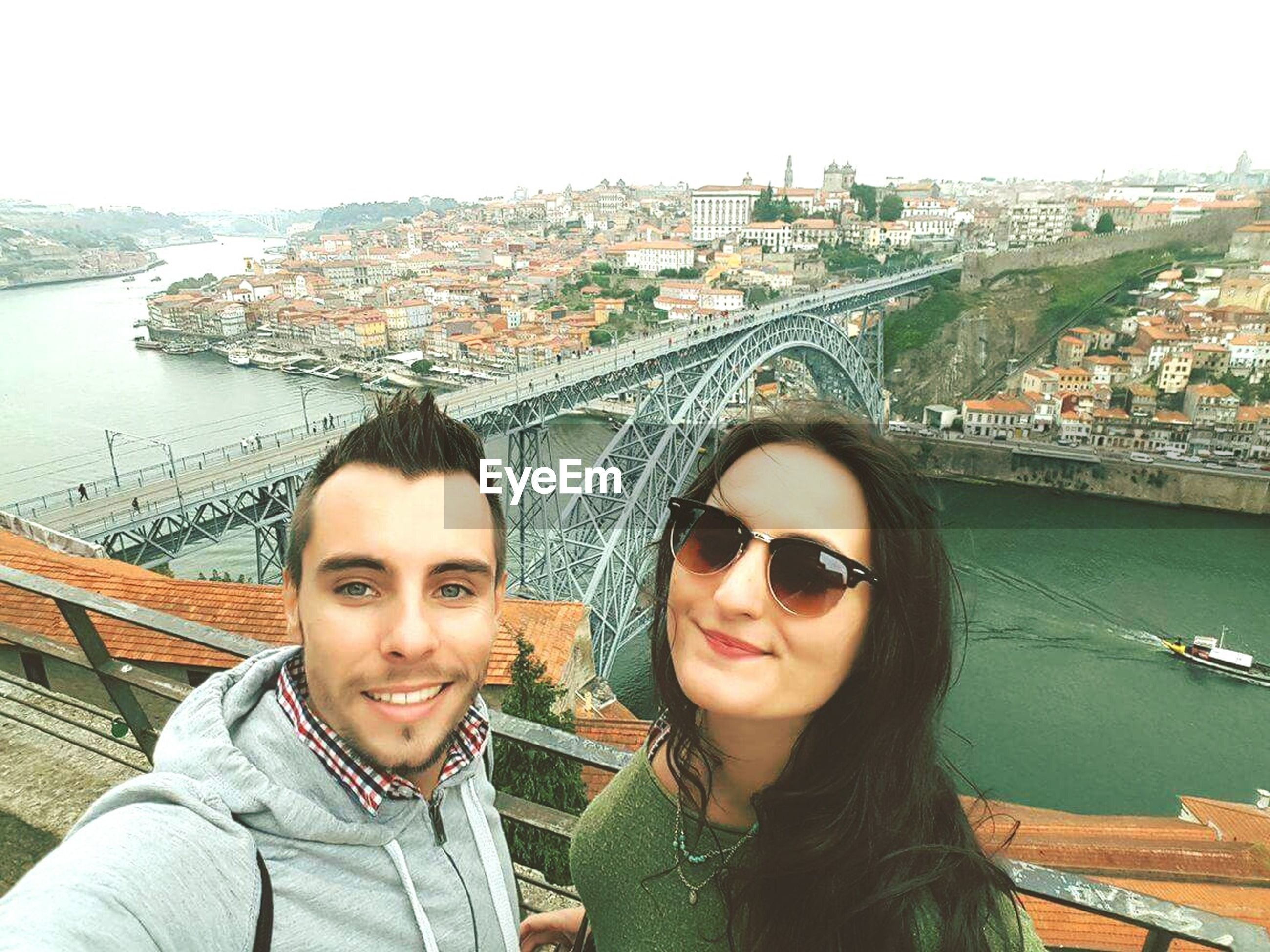 togetherness, city, architecture, leisure activity, river, young women, built structure, building exterior, portrait, looking at camera, lifestyles, cityscape, bonding, transportation, love, water, young adult, clear sky, bridge - man made structure, day, friendship, city life, casual clothing, friends, outdoors, vacations