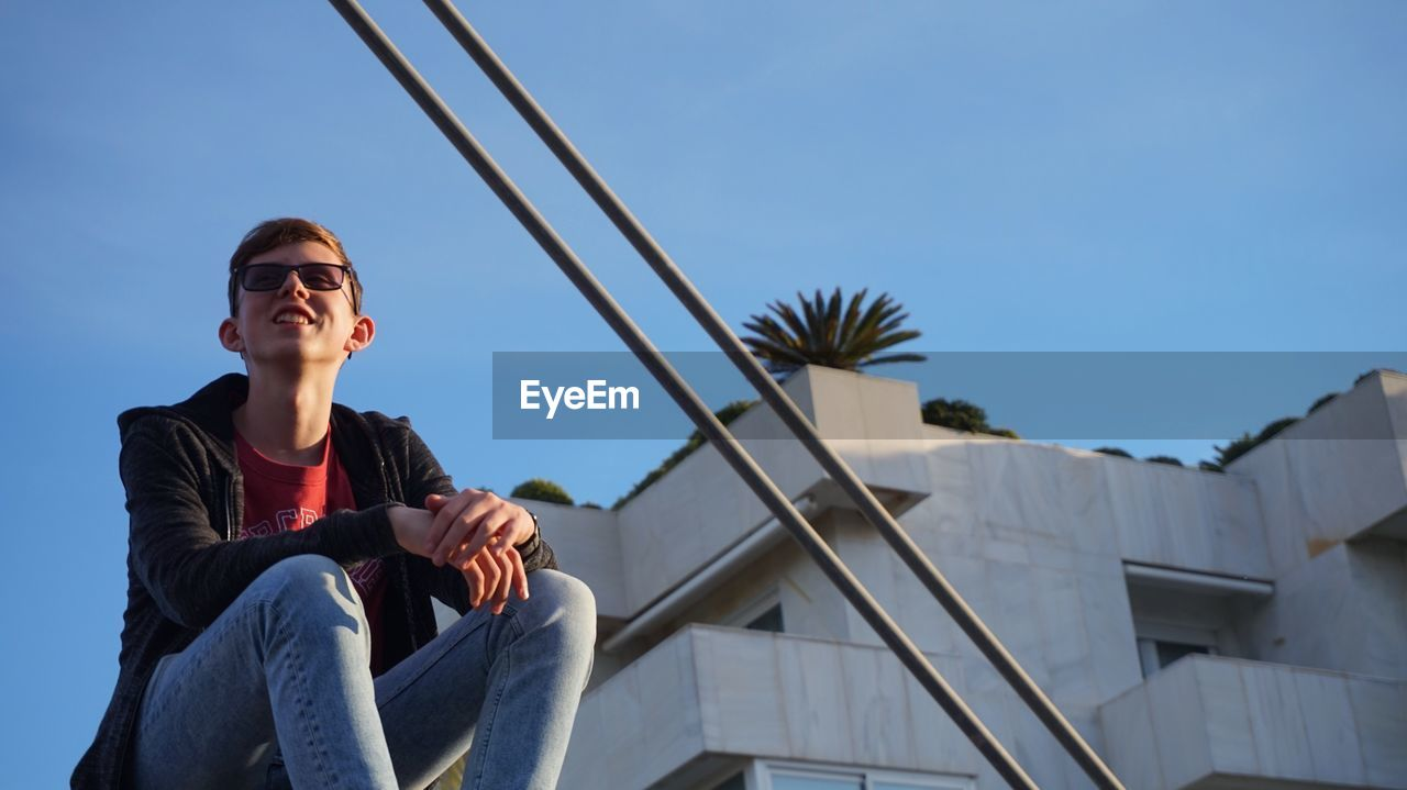 Low Angle View Of Young Man Wearing Sunglasses While Sitting On Building Terrace Against Clear Sky