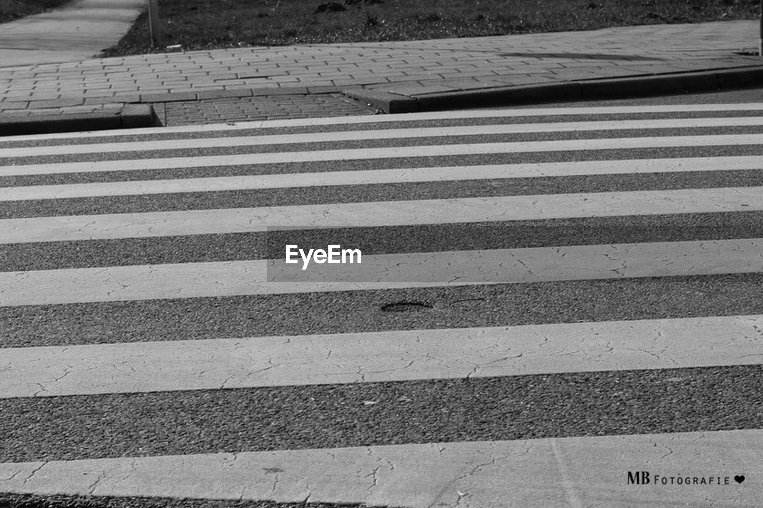 road marking, street, high angle view, asphalt, road, transportation, zebra crossing, guidance, day, outdoors, the way forward, white color, direction, arrow symbol, shadow, no people, striped, sunlight, city, directional sign
