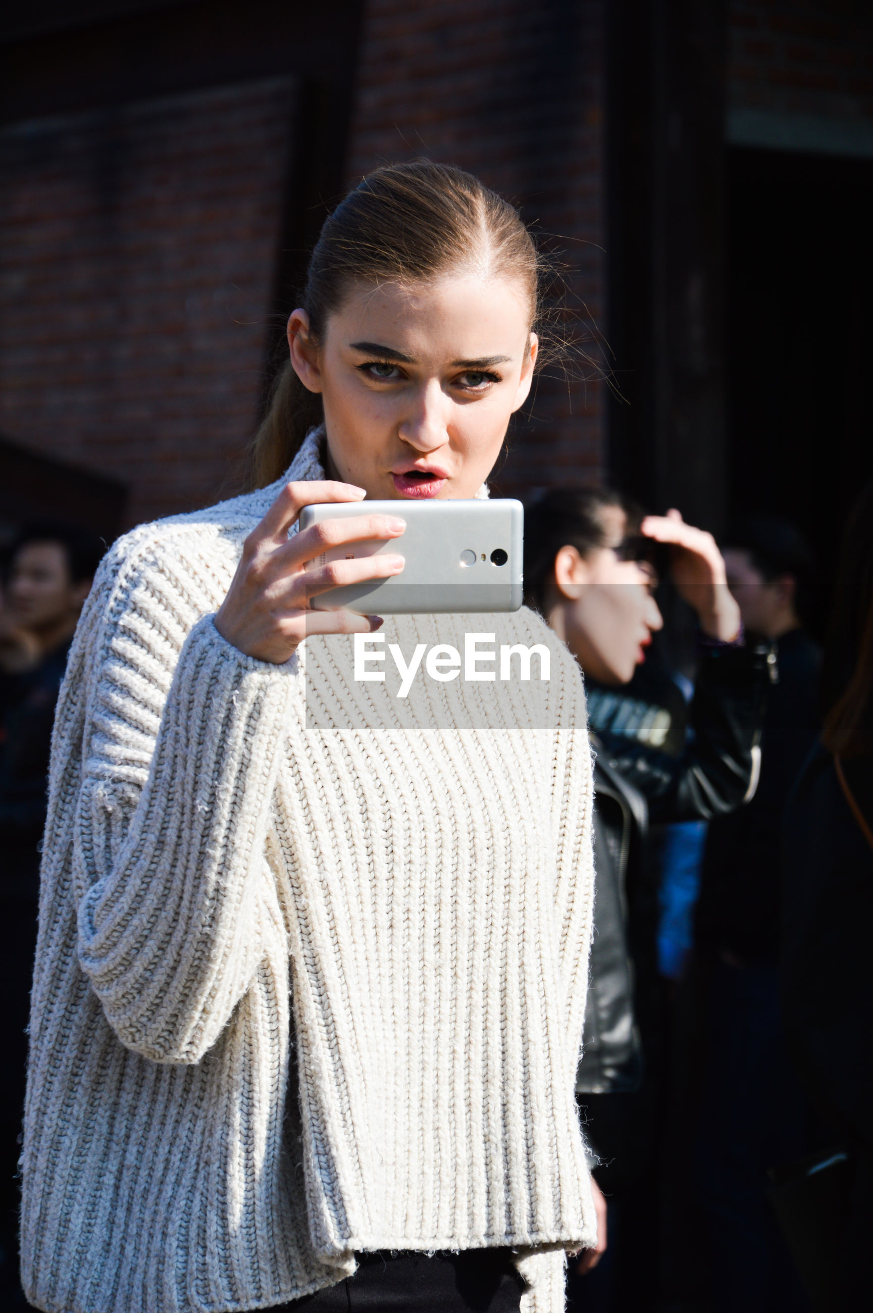 wireless technology, portable information device, smart phone, technology, communication, young adult, mobile phone, teenager, portrait, youth culture, front view, lifestyles, looking down, real people, people, women, one person, internet, adult, young women, outdoors, night