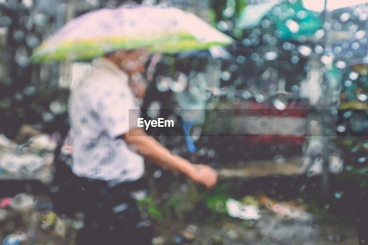 Man With Umbrella Seen From Car Window During Rainy Season