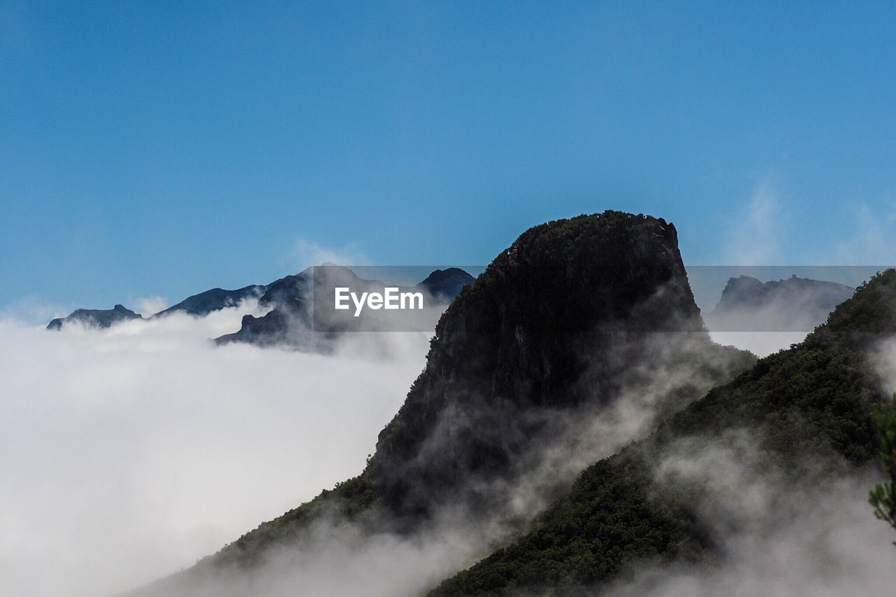 Scenic View Of Mountains Surrounded By Clouds