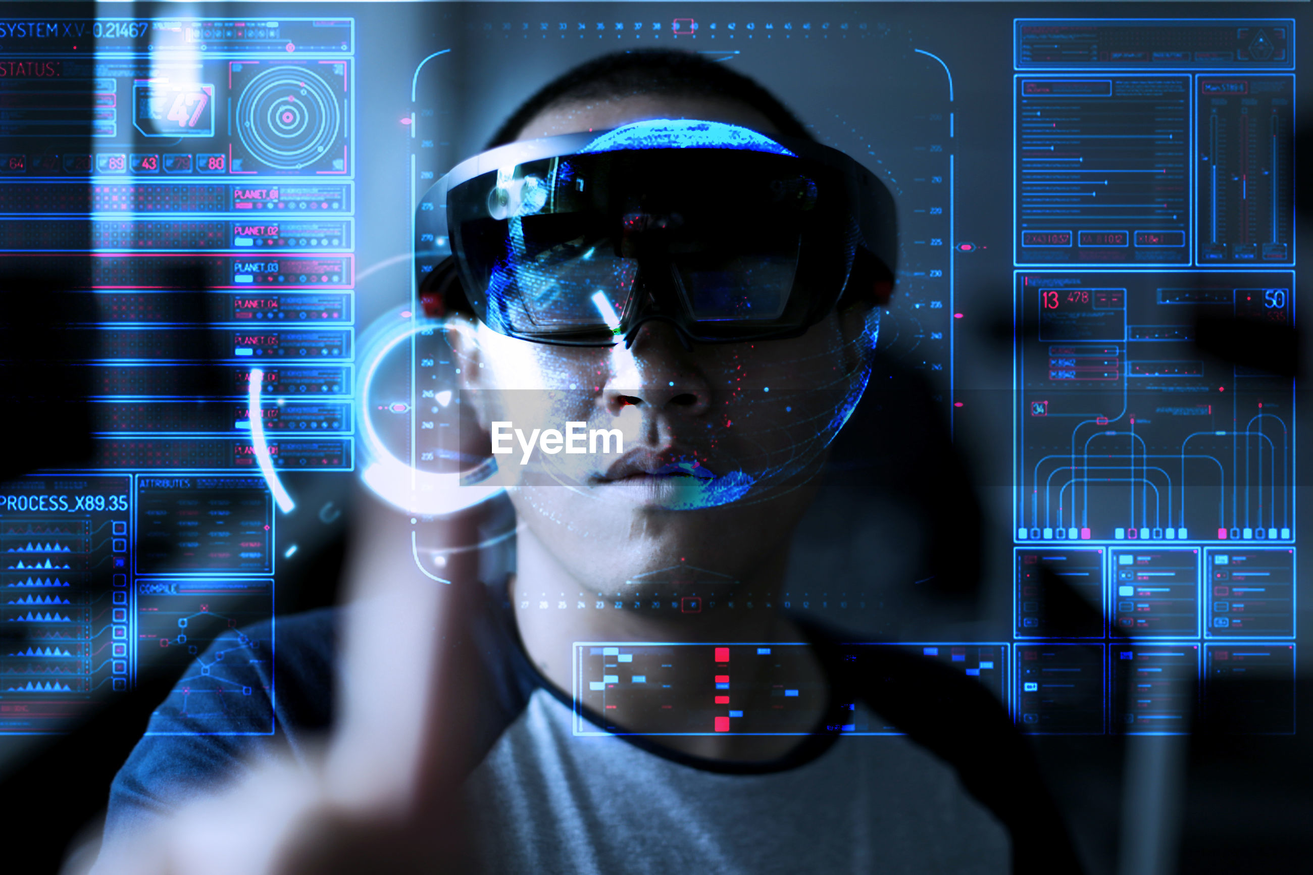 Digital composite image of young man wearing virtual reality simulator while standing with data on invisible screen