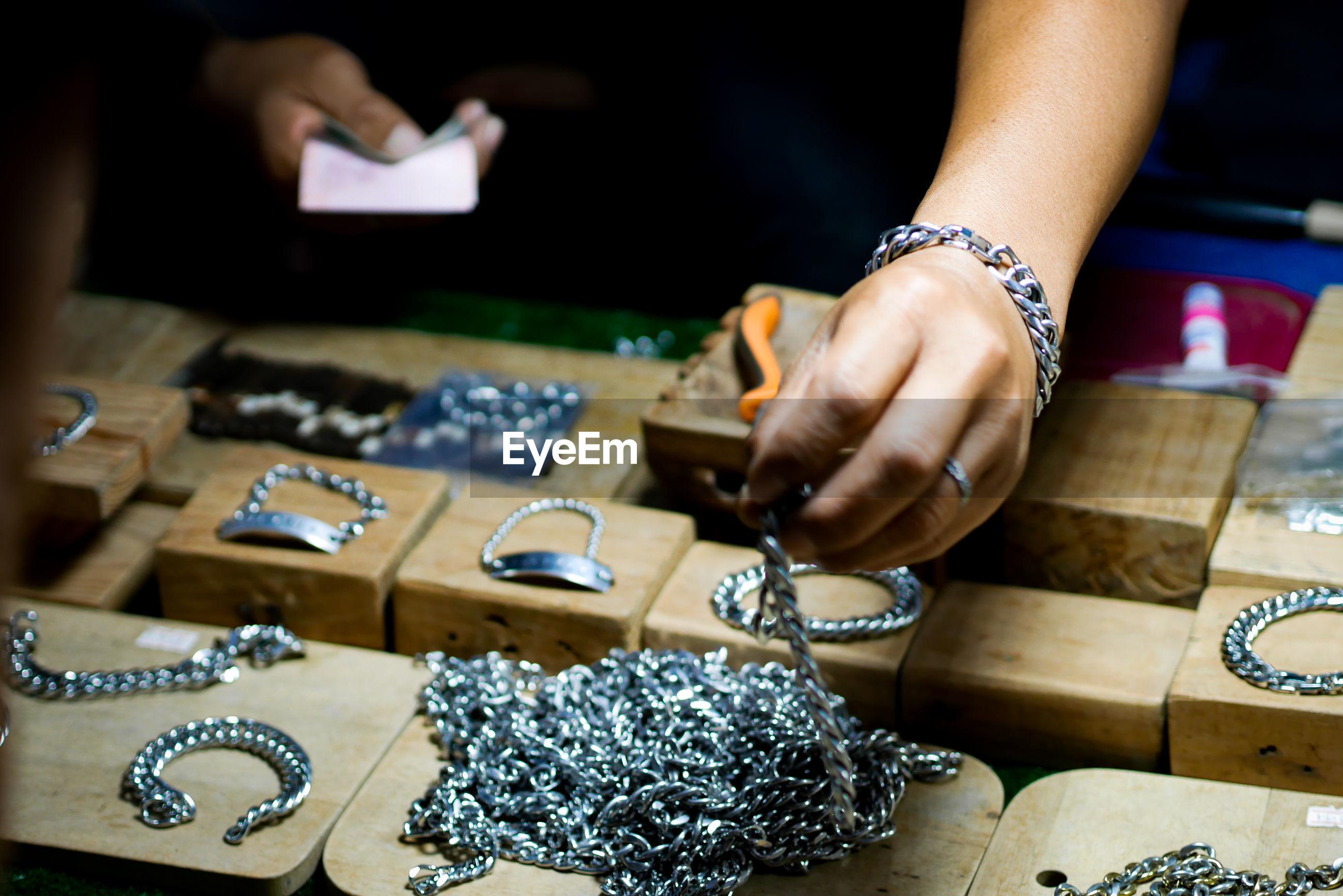 Midsection of men making bracelet