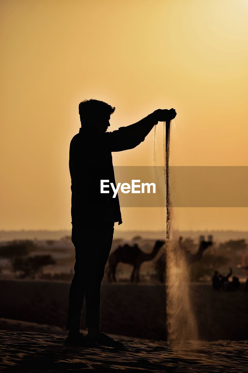 Silhouette Man Pouring Sand While Standing At Desert Against Sky During Sunset